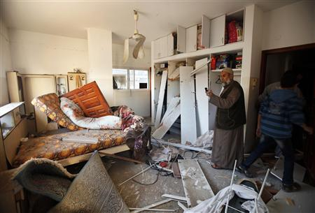 A Palestinian man takes pictures of his damaged house with a mobile phone after Israeli air strikes in Gaza City November 15, 2012. REUTERS/Suhaib Salem