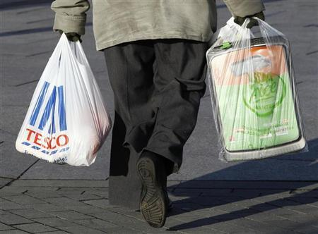 A woman carries shopping bags from Tesco and Asda in Long Eaton, central England January 12, 2012. REUTERS/Darren Staples