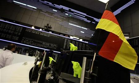 A trader's desk is decorated with a German flag and bull and a bear styrofoam figurines during morning trading session at Frankfurt's stock exchange July 7, 2011. REUTERS/Kai Pfaffenbach