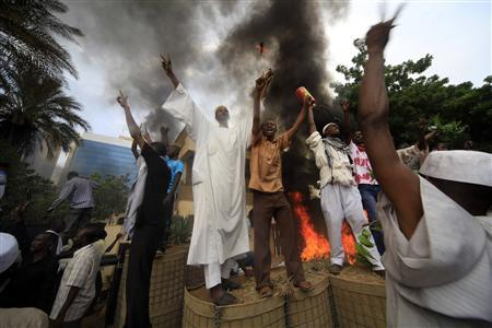 Sudanese demonstrators stand in front of the burning German embassy in Khartoum after Friday prayers September 14, 2012. REUTERS/Mohamed Nureldin Abdallah/Files