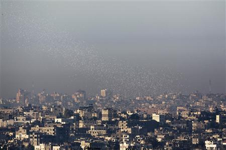 Leaflets, dropped by Israeli warplanes, telling residents to keep their distance from militants and Hamas facilities fall over Gaza, as seen from Netiv Haasara, just outside the northern Gaza Strip November 15, 2012. REUTERS/Amir Cohen