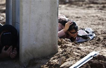 Israelis take cover as a siren sounds warning of incoming rockets in the southern town of Kiryat Malachi November 15, 2012. REUTERS/Nir Elias (ISRAEL - Tags: POLITICS CIVIL UNREST)