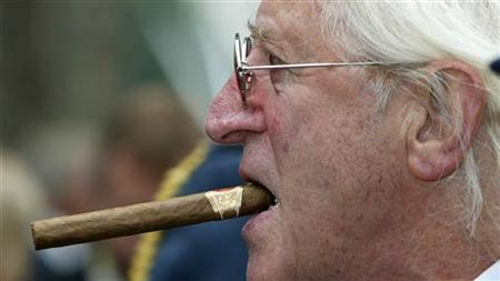 File photo of disgraced British entertainer Jimmy Savile is seen arriving at the unveiling of a new monument, commemorating the fighter pilots who fought in the Battle of Britain, in London in this September 18, 2005 file photograph. REUTERS/Paul Hackett/Files