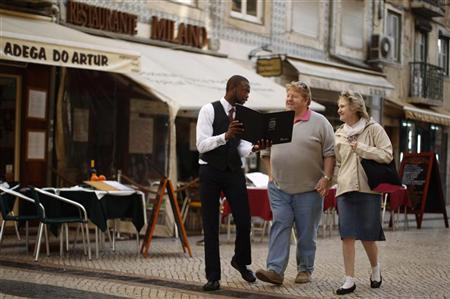 David, 23, a waiter, shows his restaurant's menu to the tourists in downtown Lisbon January 20, 2012. REUTERS/Rafael Marchante