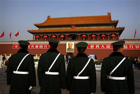 Paramilitary policemen stand guard in front of the giant portrait of former Chinese Chairman Mao Zedong at Beijing's Tiananmen Square November 15, 2012. REUTERS/David Gray (CHINA - Tags: POLITICS CRIME LAW MILITARY)