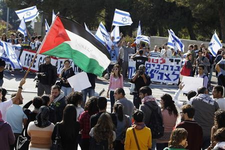 People wave Israeli flags during a demonstration supporting soldiers in Israel's military operation in Gaza, as they stand opposite a counter-protest at the Hebrew University in Jerusalem November 15, 2012. REUTERS/Ammar Awad