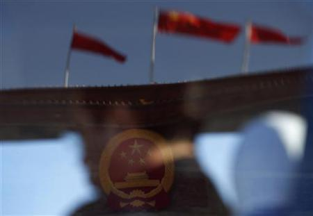 A delegate and the Great Hall of the People, the venue of the 18th National Congress of the Communist Party of China, are reflected in a window of a bus, on Tiananmen Square in Beijing, November 14, 2012. REUTERS/David Gray