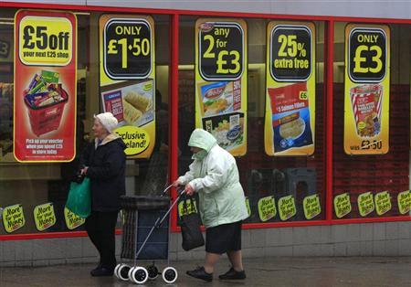 Women walk past offers advertised in the windows of a supermarket near Manchester, northern England April 25, 2012. REUTERS/Phil Noble