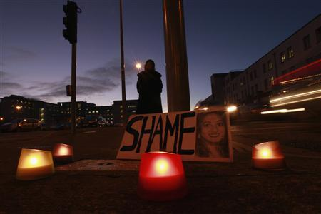 A woman holds a candlelit vigil outside University Hospital Galway in Galway, Ireland November 15, 2012. REUTERS/Cathal McNaughton