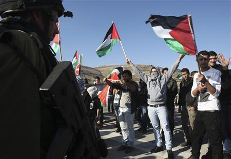 Protesters wave Palestinian flags in front of Israeli soldiers (L) during a protest against Israel's military operation in Gaza, at Hawara checkpoint near the West Bank city of Nablus November 15, 2012. REUTERS/Abed Omar Qusini