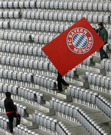 Workers of the Allianz Arena soccer stadium carry a huge poster showing the logo of German first division soccer club FC Bayern Munich at the stadium's tribune in Munich, November 24, 2005. REUTERS/Alexandra Winkler