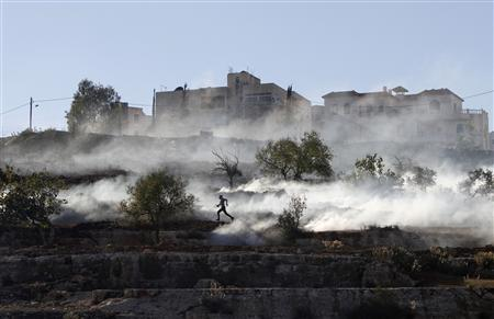 A Palestinian stone-thrower runs after Israeli security forces fired tear gas during clashes against Israel's military operation in Gaza, outside Ofer prison near the West Bank city of Ramallah November 15, 2012. REUTERS/Mohamad Torokman