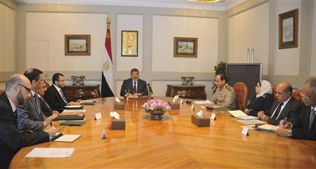 Egypt's President Mohamed Mursi (C) meets with Egypt's Prime Minister Hisham Kandil (L) and defence minister Abdel Fattah al-Sissi (R) at the presidential palace in Cairo November 15, 2012. Mursi condemned Israeli air strikes on the Gaza Strip as unacceptable on Thursday, in his harshest public criticism of Egypt's neighbour since taking office in June. REUTERS/Egyptian Presidency/Handout