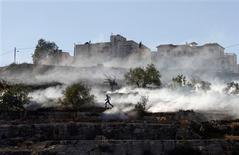 Dos proyectiles disparados desde la Franja de Gaza se lanzaron el jueves hacia Tel Aviv en el primer ataque sobre la capital comercial israelí en 20 años, subiendo las apuestas en un enfrentamiento entre Israel y los palestinos que está avanzando hacia una guerra abierta. En la imagen, un palestinoq ue estaba tirando piedras corre después de que las fuerzas de seguridad israelíes lanzaran gases lacrimógenos durante enfrentamientos contra una operación militar de Israel en Gaza, en Cisjordania, el 15 de noviembre de 2012. REUTERS/Mohamad Torokman