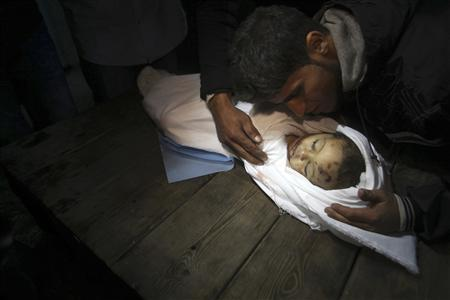 A relative mourns over the body of Palestinian baby girl Hanen Tafish who according to hospital officials was killed in an Israeli air strike in Gaza City November 15, 2012. REUTERS/Ali Hassan