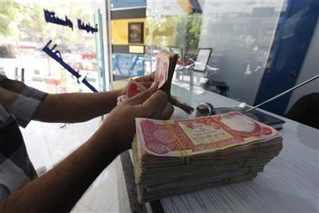 A customer counts Iraqi dinars at a money changer in Baghdad October 1, 2012. REUTERS/Saad Shalash