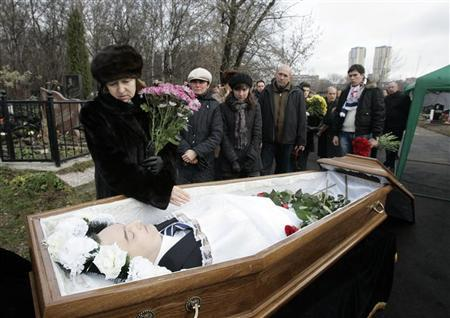 Nataliya Magnitskaya (L), mother of Sergei Magnitsky, grieves over her son's body during his funeral at a cemetery in Moscow November 20, 2009. REUTERS/Mikhail Voskresensky