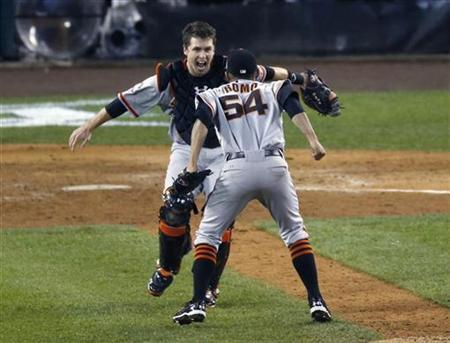 San Francisco Giants relief pitcher Sergio Romo (R) jumps into the arms of catcher Buster Posey (L) after defeating the Detroit Tigers to win the MLB World Series baseball championship in Detroit, Michigan, October 28, 2012. REUTERS/Jim Young