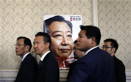 Members of the ruling Democratic Party of Japan stand next to a poster of Japanese Prime Minister Yoshihiko Noda after a meeting at the parliament in Tokyo November 15, 2012. REUTERS/Yuriko Nakao