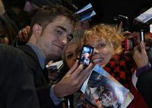 "Actor Robert Pattinson poses for a photo with a fan as he arrives for the European premiere of ""The Twilight Saga: Breaking Dawn Part 2"" in London November 14, 2012. REUTERS/Luke MacGregor"
