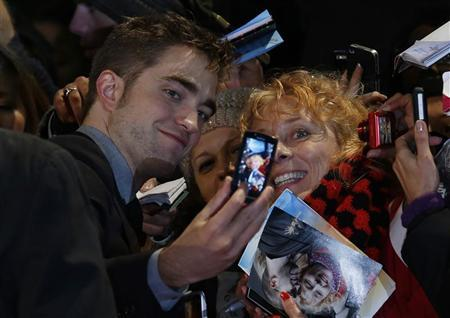 Actor Robert Pattinson poses for a photo with a fan as he arrives for the European premiere of ''The Twilight Saga: Breaking Dawn Part 2'' in London November 14, 2012. REUTERS/Luke MacGregor