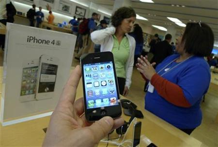 A customer (L) buys a newly-released Apple iPhone 4S at an Apple Store in Clarendon, Virginia, October 14, 2011. REUTERS/Jason Reed/Files