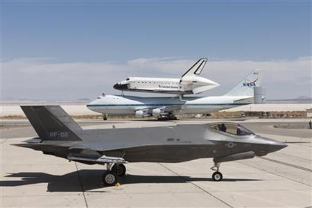 A Lockheed Martin F-35 Joint Strike Fighter (JSF) is pictured with the space shuttle Endeavour mounted atop its 747 Shuttle Carrier Aircraft (SCA) at the 461st Flight Test Squadron (FLTS) JSF Integrated Test Force at Edwards Air Force Base, California September 20, 2012. REUTERS/Paul Weatherman/Lockheed Martin/Handout/Files