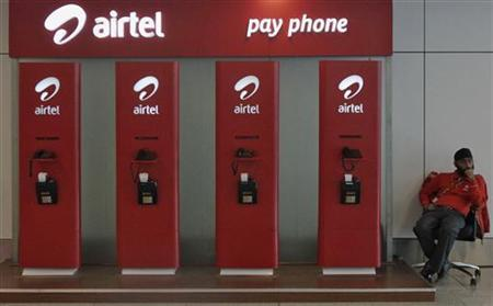 An employee sits at a Bharti Airtel public phone booth installed at the airport in New Delhi October 23, 2012. REUTERS/Vivek Prakash/Files