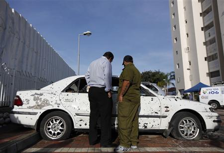 An Israeli soldier (R) and a civilian survey the damage to a car after a rocket fired from Gaza landed in the southern city of Ashdod November 16, 2012. REUTERS/Amir Cohen