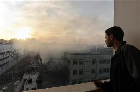 A Palestinian man looks at the building of Hamas ministry of interior damaged in an Israeli air strike in Gaza City November 16, 2012. Egypt's prime minister prepared to visit the Gaza Strip on Friday in an unprecedented display of solidarity with Hamas militants embroiled in a new escalation of conflict with Israel that risks spiralling into all-out war. REUTERS/Mohammed Salem (GAZA - Tags: CIVIL UNREST MILITARY POLITICS)