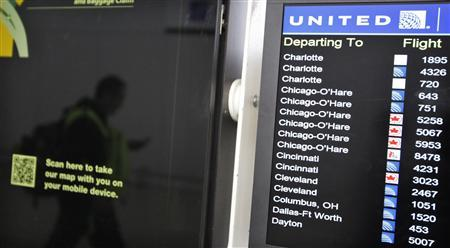 A customer is reflected in a screen showing the schedule times of United at Newark International airport in New Jersey , November 15, 2012. REUTERS/Eduardo Munoz