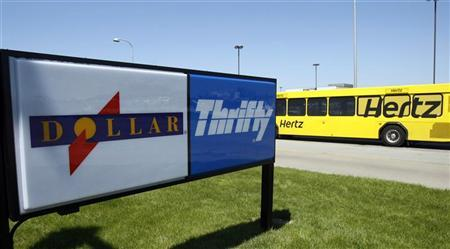 A Hertz rent-a-car shuttle bus drives by a Dollar Thrifty rent-a-car lot near the Detroit Metropolitan airport in Romulus, Michigan, May 9, 2011. REUTERS/Rebecca Cook