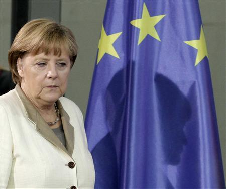 German Chancellor Angela Merkel casts her shadow on an European Union (EU) flag as she arrives for a news conference after talks with Yemen's President Abd-Rabbu Mansour Hadi in Berlin, October 4, 2012. REUTERS/Tobias Schwarz