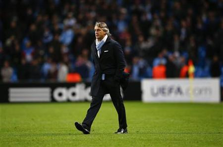 Manchester City's coach Roberto Mancini walks on the pitch to speak with officials after their Champions League Group D soccer match against Ajax Amsterdam at The Etihad Stadium in Manchester, northern England, November 6, 2012. REUTERS/Darren Staples/Files