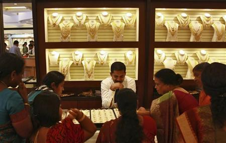 Customers check gold rings inside a gold jewellery showroom in Kochi April 16, 2012. REUTERS/Sivaram V/Files