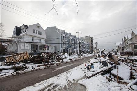 Snow left by a nor'easter, also known as a northeaster storm, covers piles of debris piled up outside of peoples homes due to the flooding from hurricane Sandy in the Queens borough neighborhood of Rockaway Beach, New York, November 8, 2012. REUTERS/Lucas Jackson