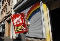 "An unidentified man removes placards of the far right National Democratic Party of Germany (NPD) from an office of the banned right-wing extremist group ""Nationaler Widerstand Dortmund"" (National Resistance Dortmund) in Dortmund August 23, 2012. REUTERS/Ina Fassbender (GERMANY - Tags: POLITICS CRIME LAW)"