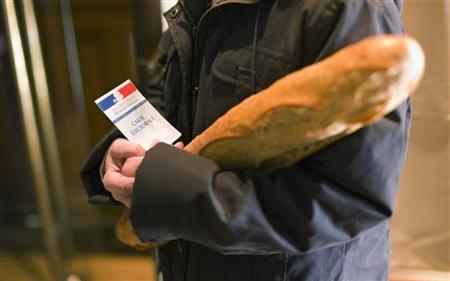 A woman holds a baguette as she votes at a polling station in Thizy, southeastern France, March 20, 2011. REUTERS/Robert Pratta/Files