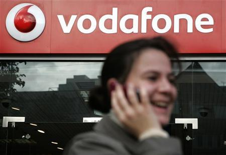 A woman talks on a mobile telephone as she passes a Vodafone store in central London November 8, 2008. REUTERS/Luke MacGregor