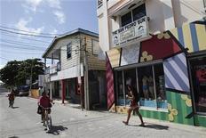 Para las muchas personas que se cruzaron en su camino en una isla tropical de Belice, era obvio que la vida de John McAfee había adoptado un giro extraño en los últimos años. El gurú del software antivirus, que fundó McAfee Associates en 1989, lleva oculto de la policía desde que ésta le quiere interrogar por el asesinato el pasado fin de semana de su vecino, el estadounidense Gregory Faull, con quien McAfee se había peleado. En la imagen, dos personas pasean en bici junto a la sede del periódico The San Pedro Sun cerca de la plaza principal de San Pedro, Belice, el 15 de noviembre de 2012. REUTERS/Henry Romero