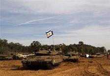 Las sirenas antiaéreas sonaron el viernes en Jerusalén, mientras el brazo armado del grupo palestino Hamás anunciaba que había disparado un proyectil Qassam hacia la ciudad. En la imagen, una bandera israelí sobre un tanque en la frontera con la Franja de Gaza, el 16 de noviembre de 2012. REUTERS/Ronen Zvulun