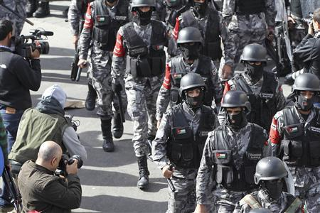 Riot policemen stand guard as protesters from the Islamic Action Front and other opposition parties demonstrate following an announcement that Jordan would raise fuel prices, including a hike on cooking gas, after Friday prayers in Amman November 16, 2012. REUTERS/Muhammad Hamed