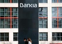 Las negociaciones con Bruselas respecto a la quita que se aplicará a la deuda subordinada y preferente de la nacionalizada Bankia siguen vivas sobre la base de un descuento inferior al 50 por ciento, dijo una fuente que participa en las negociaciones. En la imagen, mujeres frente a la sede de Bankia en Madrid, el 26 de octubre de 2012. REUTERS/Sergio Pérez