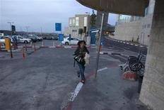 An Israeli woman runs to take cover as an air raid siren warns of incoming rockets at the parking lot of a hospital in Jerusalem November 16, 2012. REUTERS/Baz Ratner