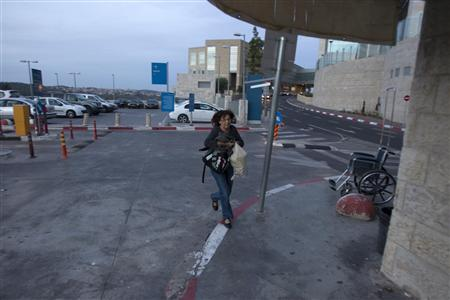 An Israeli woman runs to take cover as an air raid siren warns of incoming rockets at the parking lot of a hospital in Jerusalem November 16, 2012. REUTERS/Baz Ratner