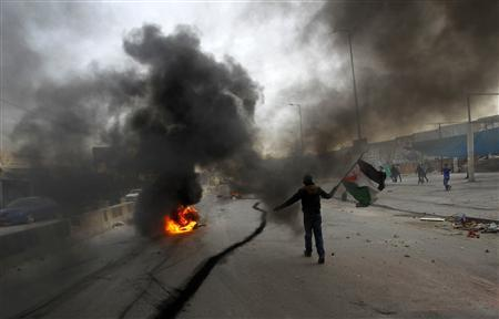 A Palestinian stone-thrower walks past smoke from burning tyres during clashes with Israeli security forces against Israel's military operation in Gaza, at Qalandia checkpoint near the West Bank city of Ramallah November 16, 2012. REUTERS-Mohamad Torokman