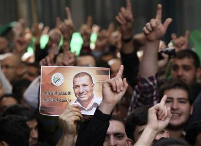 Palestinian protesters hold a placard depicting Ahmed Jaabari, slain Hamas's military mastermind, during a demonstration supporting Hamas in the West Bank city of Nablus November 16, 2012. REUTERS-Abed Omar Qusini
