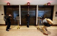 El ex director de la CIA David Petraeus dijo el viernes al Congreso que la agencia de espionaje y él habían intentado dejar claro desde el principio que personas afiliadas a Al Qaeda participaron en el ataque de septiembre a la delegación diplomática de EEUU en Bengasi, Libia, según parlamentarios. En la imagen, una fotógrada es fotografiada mientras intenta enfocar a través de una rendija en la puerta donde se celebra la comparecencia apuerta cerrada del ex general Petraeus en el Senado de EEUU, Washington, el 16 de noviembre de 2012. REUTERS/Kevin Lamarque