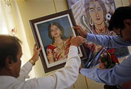 Andanappa Yalagi (L), father of Savita Halappanavar, is helped by a family friend as he hangs her portrait at their house in Belgaum in Karnataka November 16, 2012. REUTERS/Danish Siddiqui