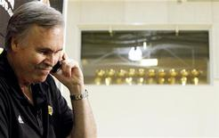 New Los Angeles Lakers head coach Mike D'Antoni is interviewed over a mobile phone as Lakers' championship trophies are seen in a window above the Lakers' practice court following a media conference at the Lakers' training facility in El Segundo, California November 15, 2012. REUTERS/Danny Moloshok
